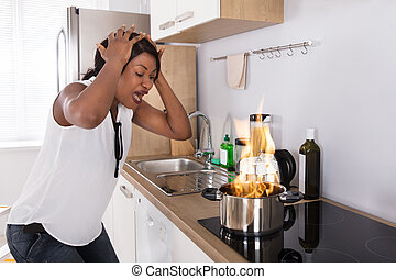 Frustrated Woman Looking At Utensil On Fire