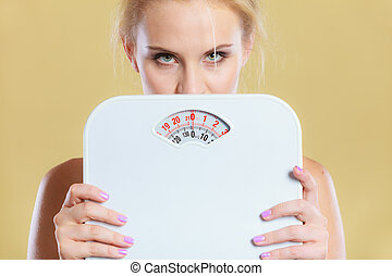 Frustrated sad blonde girl covering her face with scales. Weight gain, time for slimming weightloss, diet.