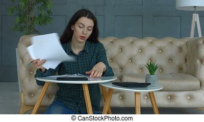Stressed woman doing her finances, reviewing bills and bank receipts being thoughtful and worried while sitting in domestic room. Desperate woman with many debts throwing away unpaid bills at home.