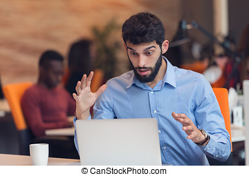 frustrated young business man working on desktop computer