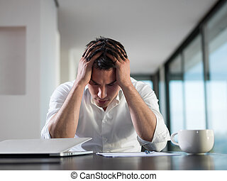 frustrated young business man working on laptop computer at home