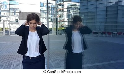 Frustrated young business woman walking near office