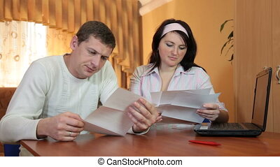 Frustrated young husband and wife who read some bad news in...