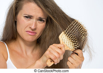 Frustrated young woman combing hair