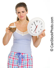 Frustrated young woman in pajamas with cup and clock