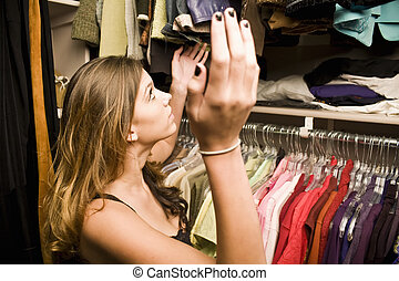 Young woman frustrated looking through her closet trying to find clothes