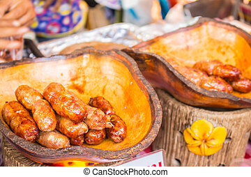 sausages in a wooden tray.