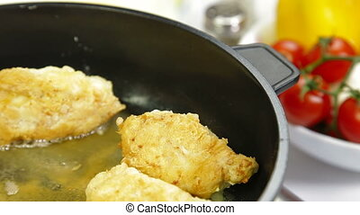 frying chicken breast roll on a frying pan. Closeup