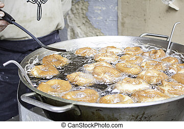 Frying donuts - Pan frying donuts in market feed, dessert