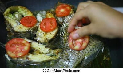Frying fish in a grill pan with tomatoes, cheese and dill
