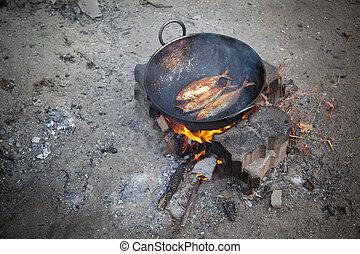 Frying fish in open