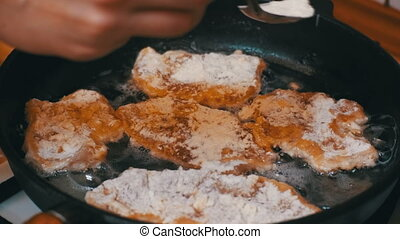 Frying Meat Chops on a Frying Pan in the Home Kitchen