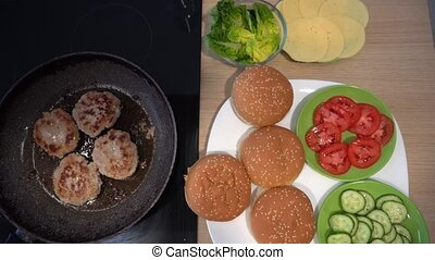 Frying meatballs in a pan and burger ingredients. Vegetables bun and cheese