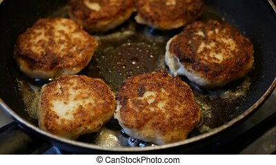 frying of fish cakes in a pan