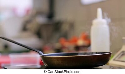 frying pan on cooker in kitchen - cooking, food and culinary...