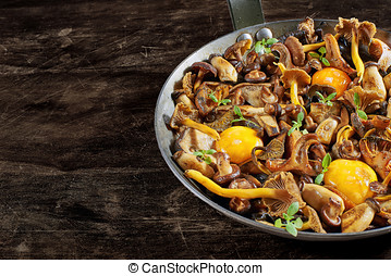 Frying pan steel with mushrooms and soft egg yolks.
