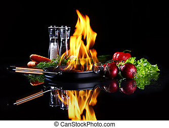 Frying pan with burning fire inside and fresh vegetables ...