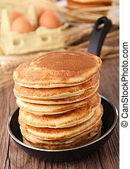 frying pan with pancakes and ingredients