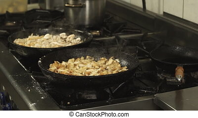 frying pans or skillets with pieces of meat are on the gas stove in restaurant kitchen