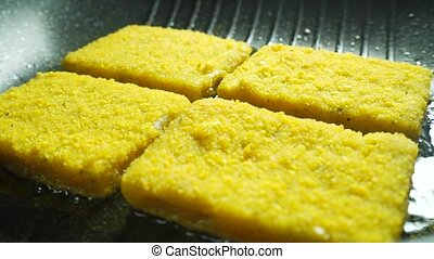 Frying pieces of breaded fish fillet, close up shot