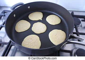 Frying Pikelets in a fry pan on a stove.