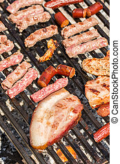 Frying pork and chicken meat on the barbecue grill