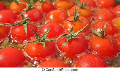 Frying red cherry tomatoes with leaves, close up shot