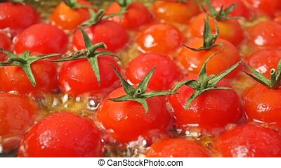 Frying ripe red cherry tomatoes. Close up dolly shot
