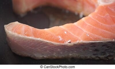 Frying salmon steak on anti-stick frying pan. Macro dolly...