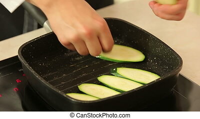 Frying sliced zucchini in a pan