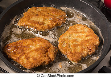 Frying wiener schnitzel in a hot pan