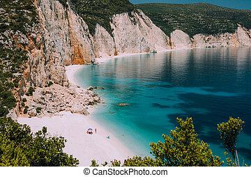 Fteri beach. Blue lagoon with rocky coastline, Kefalonia, Greece. Calm clear blue emerald green turquoise sea water with dark deep pattern