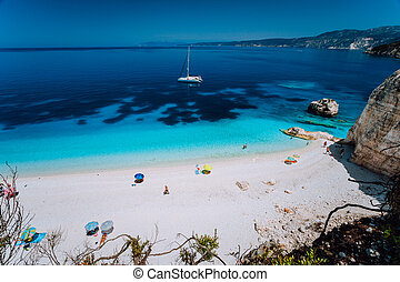 Fteri beach, Cephalonia Kefalonia, Greece. White catamaran yacht in clear deep blue sea water with amazing dark pattern on the bottom. Tourists on sandy beach near azure lagoon
