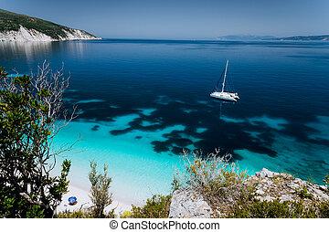 Fteri beach, Cephalonia Kefalonia, Greece. White catamaran yacht on clear transparent blue azure sea water surface. Paradise beach