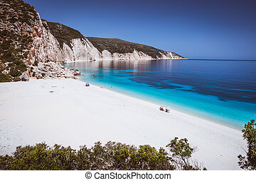 Fteri beach, Kefalonia, Greece. Lonely tourists protected from sun umbrella chill relax near clear blue emerald turquoise sea water lagoon. Framed by tree foliage