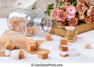 Fudge candy and caramel on baking paper and in glass jar, ...