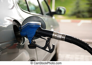 fuelling nozzle inserted into petrol tank at gas station for gasoline filling