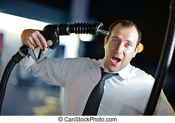 Fuel problem - Businessman putting gas nozzle to his head, ...