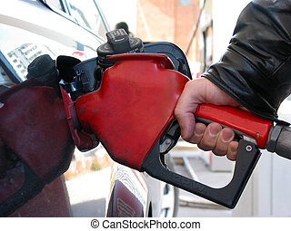 Fuel pump hand - Hand holding a has pump nozzle fueling a...