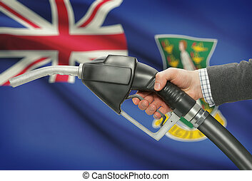 Fuel pump nozzle in hand with national flag on background - British Virgin Islands