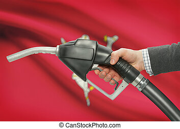 Fuel pump nozzle in hand with national flag on background - Isle of Man