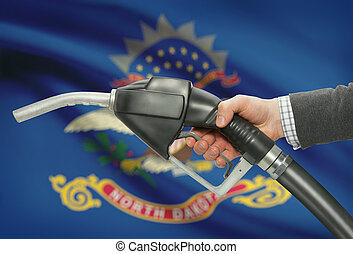 Fuel pump nozzle in hand with US states flags on background - North Dakota