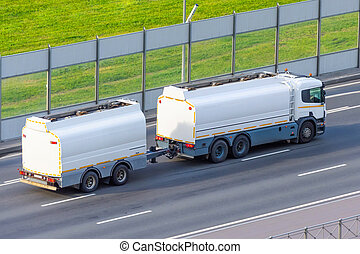 Fuel tanker truck with fuel tank trailer driving on highway.