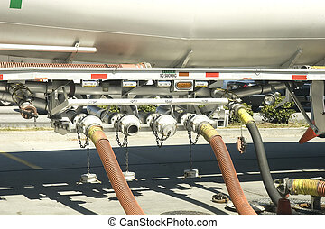 Hoses coupled to a fuel truck transferring gasoline to tanks at a service station