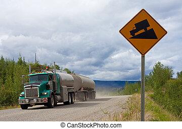 Fuel truck on steep dirt road - Loaded fuel tanker semi-...
