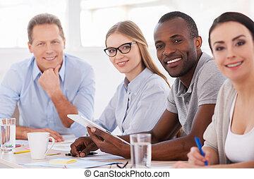 fuerte, y, creativo, team., grupo de empresarios, sentado, consecutivo, en la mesa, y, sonriente, en cámara del juez