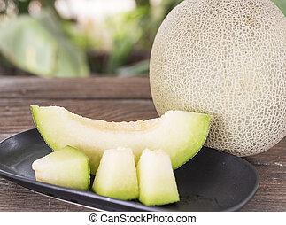 melon - Full and sliced ??cantaloupe melon on wooden floor.