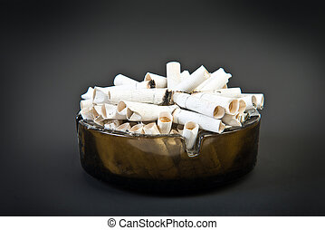 Full ashtray with butts over black