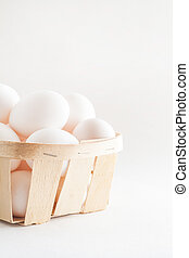 full basket of fresh eggs on a white background