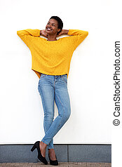 Full body beautiful young african american woman smiling against white wall with hands behind head